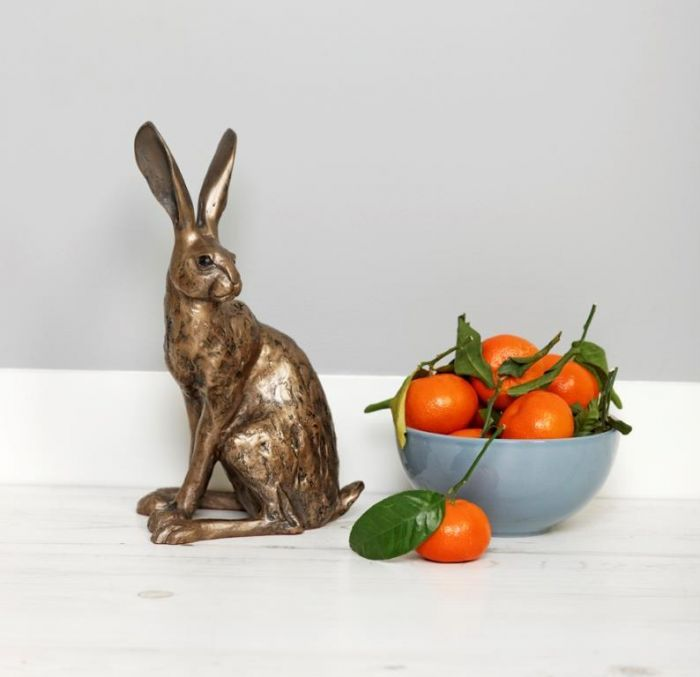 Bronze sitting hare sculpture in a home setting next to a bowl of oranges