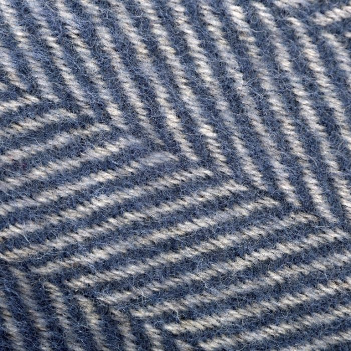 An oblique detailed view of the herringbone pattern on this blue throw, showing how soft the throw looks