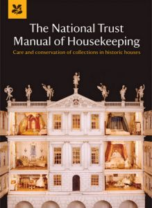 The front cover of the National Trust Manual of Housekeeping book with dolls house on a black background