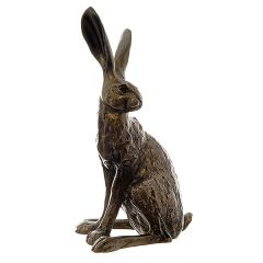 A sculpted bronze resin hare, sitting upright with his ears pricked, looking over his left shoulder