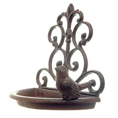 A cast iron wall mounted bird feeder with scroll detailing and a small bird perched on the edge of a semi circular dish