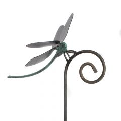 Detail of a green bodied dragonfly with black metal wings on a curved black stake
