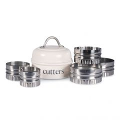 The cream pastry cutter tin surrounded by stainless steel tin cutters of varying sizes stacked to the left and right
