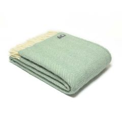 Looking down onto the herringbone pattern seafoam green folded throw with cream tassles