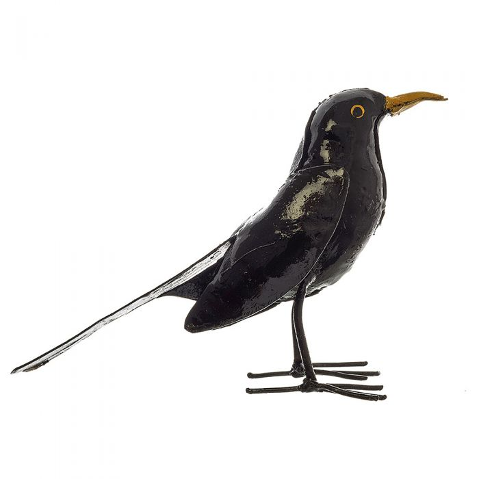 A side profile of a standing glossy laquered blackbird with bright yellow beak, made from recycled metal